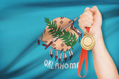 Medal in hand with flag on background - State of Oklahoma. Part of a series. — Photo
