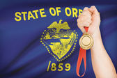 Medal in hand with flag on background - State of Oregon. Part of a series. — Stock Photo