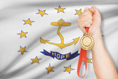 Medal in hand with flag on background - State of Rhode Island and Providence Plantations. Part of a series. — Stock Photo