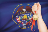 Medal in hand with flag on background - State of Utah. Part of a series. — Stock Photo