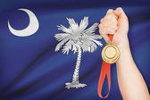 Medal in hand with flag on background - State of South Carolina. Part of a series. — Stock Photo