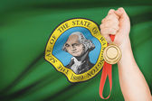 Medal in hand with flag on background - State of Washington. Part of a series. — Stock Photo