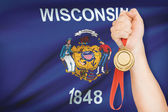 Medal in hand with flag on background - State of Wisconsin. Part of a series. — Stock Photo