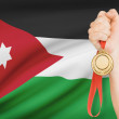 Medal in hand with flag on background - Hashemite Kingdom of Jordan — Stock Photo