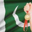 Medal in hand with flag on background - Islamic Republic of Pakistan — Stock Photo