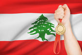 Medal in hand with flag on background - Republic of Lebanon — Stock Photo