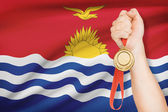 Medal in hand with flag on background - Republic of Kiribati — Stock Photo