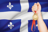 Medal in hand with flag on background - Quebec — Stock Photo