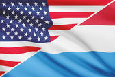 Series of ruffled flags. USA and Grand Duchy of Luxembourg. — Stock Photo