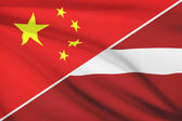 Series of ruffled flags. China and Republic of Latvia. — Stock Photo