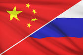 Series of ruffled flags. China and Russian Federation. — Stock Photo