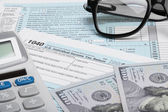 United States of America Tax Form 1040 with calculator, dollars and glasses — Stock Photo