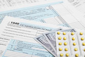 United States of America Tax Form 1040 with dollars and pills — Stock Photo