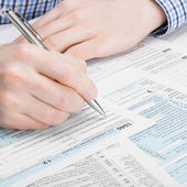 United States of America Tax Form 1040 - man performing tax calculation - 1 to 1 ratio — Stock Photo