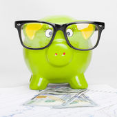 Green piggy bank over stock market chart with 100 dollars banknote - 1 to 1 ratio — Stock Photo
