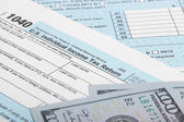 US Tax Form 1040 with 100 US dollar bills — Stock Photo