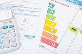 Calculator with utility bill and energy rating chart — Stock Photo