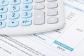 Calculator over utility bill - studio shot — Stock Photo