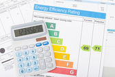 Calculator with utility bill and energy efficiency chart — Stock Photo