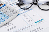 Studio shot of calculator and glasses over some receipt — Stock Photo