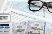 USA Tax Form 1040 with glasses, calculator and 100 US dollar bills — Stock Photo
