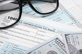 USA Tax Form 1040 with glasses and 100 US dollar bills — Stock Photo