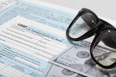 USA 1040 Tax Form with glasses and two 100 US dollar bills — Stock Photo