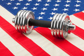 Dumbbell weights over USA flag as symbol of healthy nation — Stock Photo