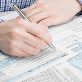 United States of America Tax Form 1040 - man performing tax calculations - 1 to 1 ratio — Stock Photo