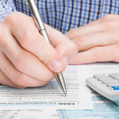 United States of America Tax Form 1040 - male filling out tax form - 1 to 1 ratio — Stock Photo