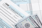 USA 1040 Tax Form with two 100 US dollar banknotes over it - studio shoot — ストック写真