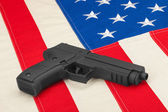 Handgun laying on USA flag - studio shoot — Stock Photo
