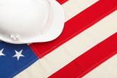Construction protective helmet laying USA flag - studio shoot — Stock Photo