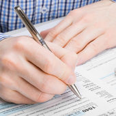 Male filling out 1040 United States of America Tax Form - studio shoot - 1 to 1 ratio — Stock Photo