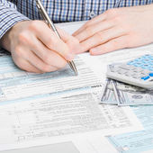 Male filling out 1040 USA Tax Form - studio shoot - 1 to 1 ratio — Stock Photo