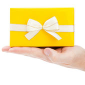 Yellow gift box with golden edge ribbon on male palm - 1 to 1 ratio — 图库照片