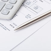 Studio shot of calculator and pen over some receipt - 1 to 1 ratio — Stock Photo