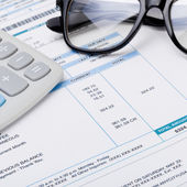Studio shot of calculator and glasses over some receipt - 1 to 1 ratio — Stock Photo