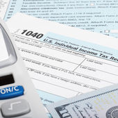 US Tax Form 1040 with calculator and 100 US dollar bills — Stock Photo