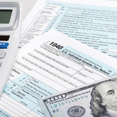 USA Tax Form 1040 with calculator and 100 US dollar bills — Stock Photo