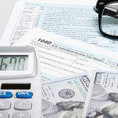 USA Tax Form 1040 with glasses, calculator and 100 US dollar bil — Stock fotografie