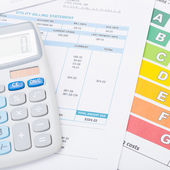 Calculator with utility bill and energy rating chart under it - 1 to 1 ratio — Stock Photo
