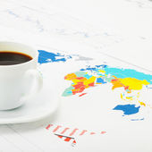 White coffee cup over world map and financial documents - studio shot - 1 to 1 ratio — Stock Photo