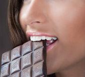 Girl eating chocolate — Stock Photo