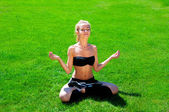 A young athlete meditates on the grass — Stock Photo