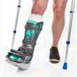 Man with a broken leg with Crutches on a white background - Stock Photo