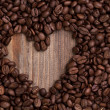Heart shape made from coffee beans on wooden table — Stock Photo