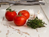 Tomatoes, garlic and thyme on a white wooden table — Stock Photo