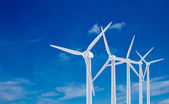 White wind turbine generating electricity on blue sky — Stock Photo