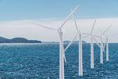 White wind turbine generating electricity on the sea — Stock Photo